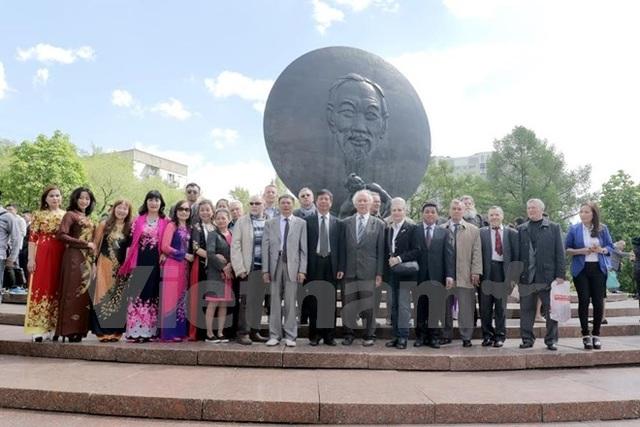 Chụp ảnh lưu niệm trước Tượng đài Bác Hồ ở thủ đô Moskva. (Ảnh: Quang Vinh/Vietnam+)