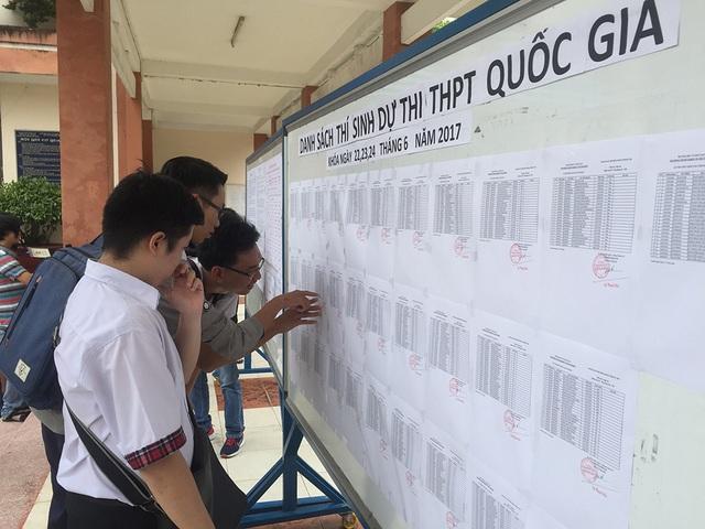 Thí sinh tại điểm thi trường THPT Nguyễn Hữu Huân có mặt sớm xem thông tin trước giờ vào làm thủ tục