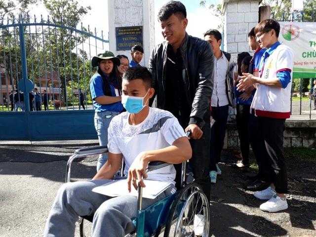 Lê Văn Hào được người bạn cùng đơn vị giúp đỡ việc đi lại vào phòng thi bằng xe lăn. (Ảnh: Ngọc Hà)