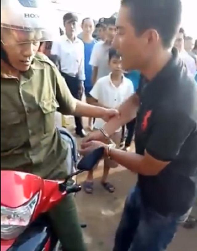 Một công an xã còng tay và chở người đàn ông đi bằng xe máy vì nghi người này là bắt cóc trẻ em. (Ảnh cắt từ clip)