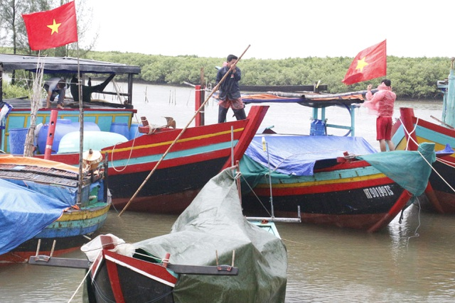 Ngư dân khẩn trương giằng néo lại tàu thuyền để đối phó với bão