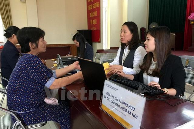 Người dân TP Hà Nội lãnh lương hưu ở bưu điện. (Ảnh: T.H/Vietnam+)