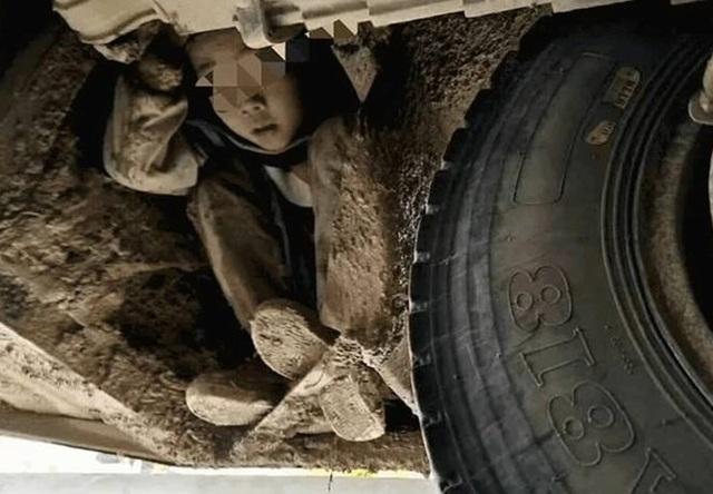 Một cậu bé trốn dưới gầm xe. (Nguồn: CGTN)