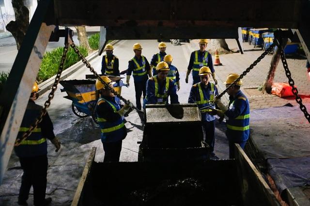 Những công nhân nạo vét bùn ở hồ Hoàn Kiếm theo kế hoạch làm sạch lòng hồ của TP.Hà Nội.