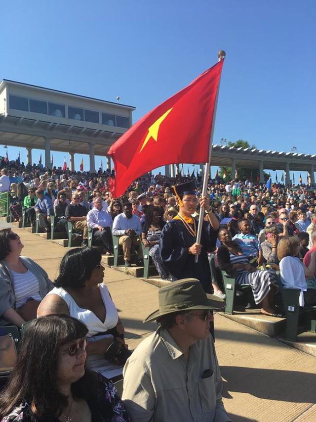 Lê Quang Liêm cầm cờ Tổ quốc trong buổi tốt nghiệp ĐH tại Mỹ.