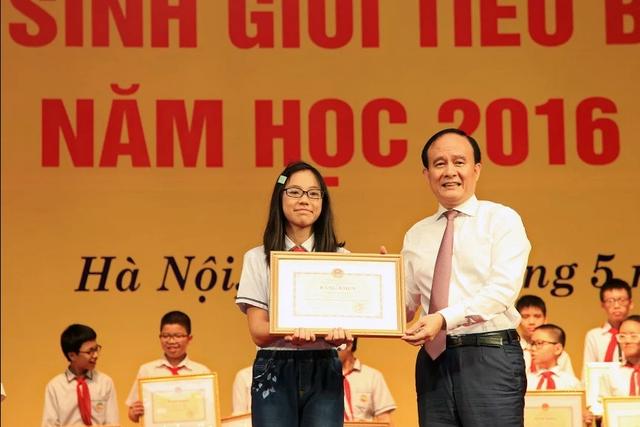 Phó Chủ tịch Thường trực HĐND TP Nguyễn Ngọc Tuấn trao bằng khen cho các học sinh.