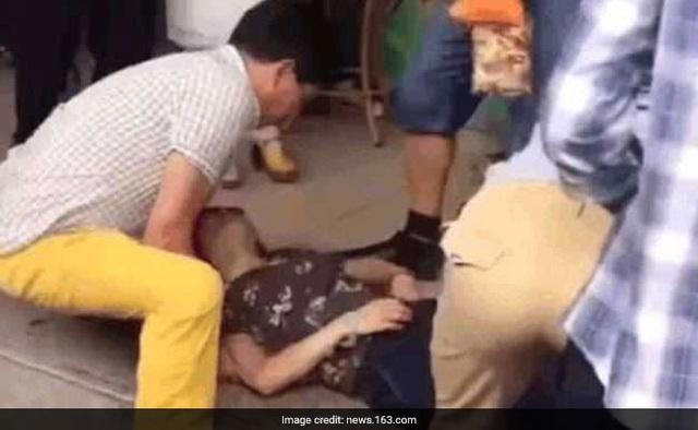 Người đi đường cố gắng giúp đỡ người phụ nữ sau khi cô ngất xỉu. (Nguồn: Handout)