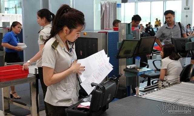 Nhân viên an ninh Nguyễn Thị Bích Ngọc kiểm tra giấy tờ liên quan đến một chiếc máy lạ mắt