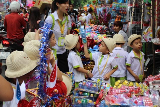 Giữa đồ chơi truyền thống và đồ chơi hiện đại, đứa trẻ này chọn đồ chơi hiện đại. (Ảnh: Hồng Vân)