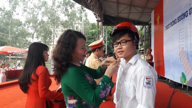 Thứ trưởng Bộ GD&ĐT Nguyễn Thị Nghĩa giúp một em HS đội mũ bảo hiểm tại buổi lễ ra quân