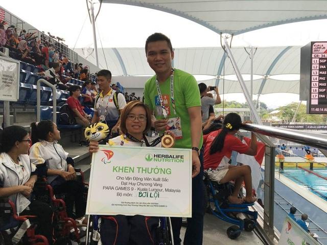VĐV bơi lội Vi Thị Hằng khi nhận thưởng nóng từ đại diện Herbalife VN tại Malaysia
