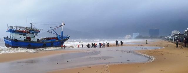 Lực lượng chức năng nỗ lực cứu hộ tàu cá của  ngư dân Phú Yên bị sóng đánh dạt vào biển Quy Nhơn, tỉnh Bình Định (ảnh Doãn Công)