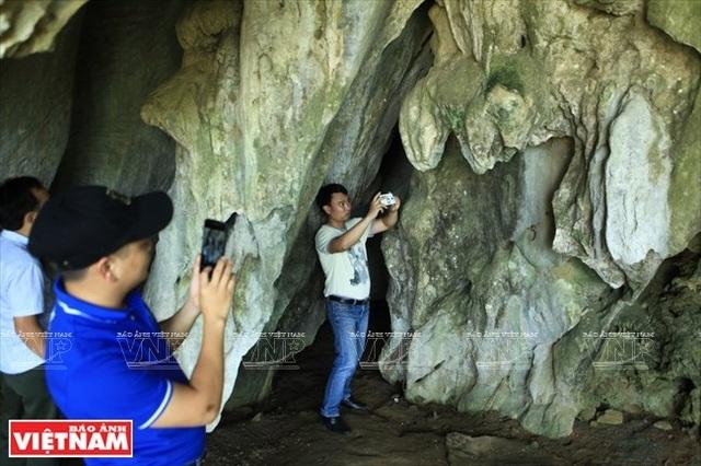Du khách thích thú ghi lại hình ảnh nhũ đá có hình thù độc đáo bên cạnh bia Ma Nhai.