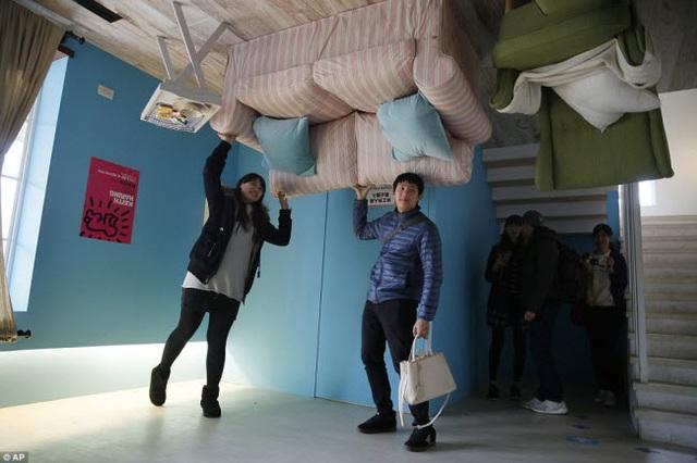 Du khách chụp ảnh với những đồ nội thất bị đảo ngược trong ngôi nhà ở Đài Bắc.