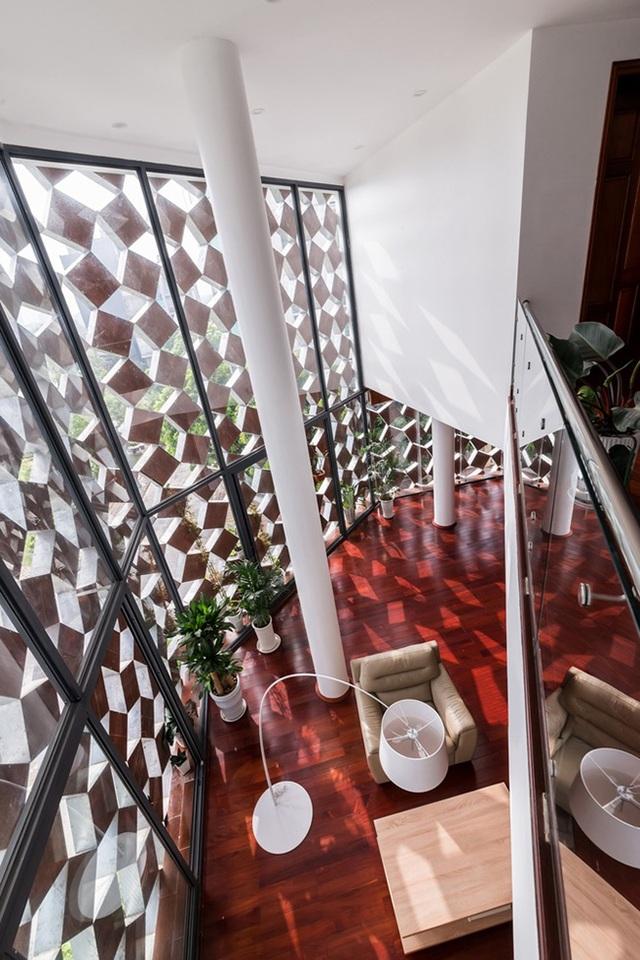 Phòng khách được tận dụng đặt dưới khoảng trần mở, mang đến không gian thoáng rộng.