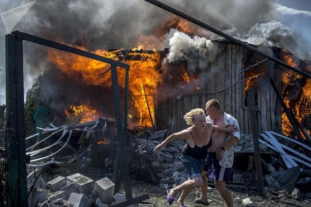 Người dân địa phương tại làng Luganskaya, khu vực Donbass, miền Đông Ukraine, vùng chạy ra khỏi ngôi nhà bị trúng bom. Ảnh: Sputnik.