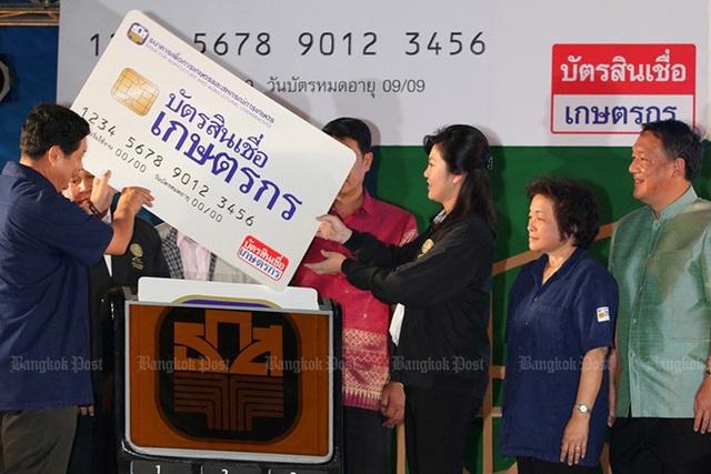 Bà Yingluck trao biểu tượng chiếc thẻ tín dụng nông dân đầu tiên cho đại diện 18 tỉnh vùng Đông Bắc Thái Lan ngày 30/7/2012. Ảnh: Bangkok Post