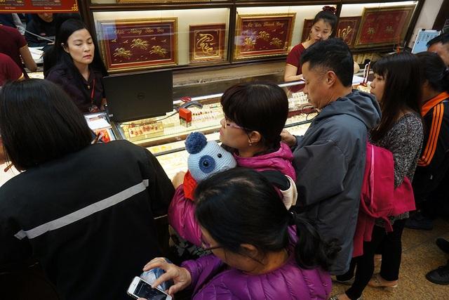 6h30, cửaa hàng mở cửa, chị Hương cùng con nhỏ được vào mua vàng trong nhóm khách đầu tiên.