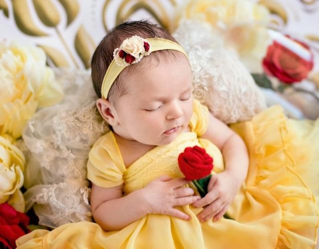 Diện bộ váy vàng rực và cầm trong tay đóa hồng chứa lời nguyền