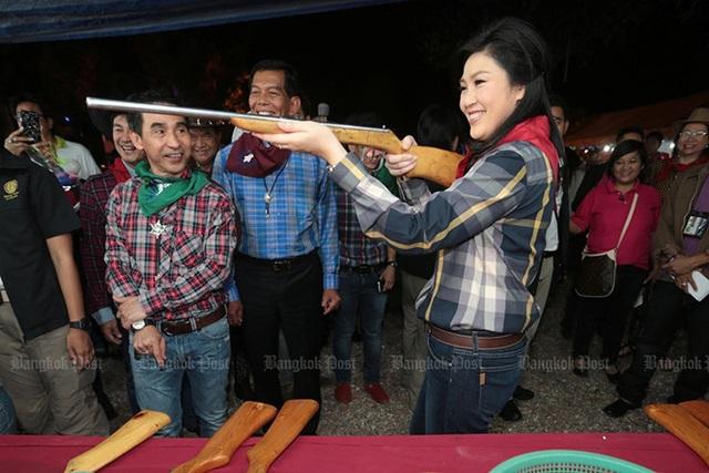 Bà Yingluck ngắm bắn bằng một khẩu súng tự chế khi tham gia hội chợ tổ chức dành riêng cho thành viên đảng Pheu Thai tại một khu nghỉ mát ở Khao Yai (Nakhon Ratchasima, Thái Lan) ngày 7/1/2013. Ảnh: Bangkok Post
