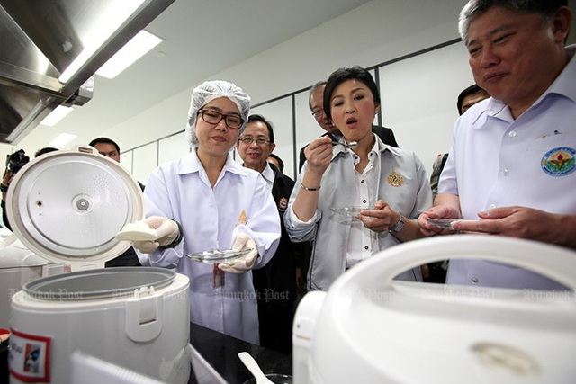 Bà Yingluck kiểm tra một công ty của Tập đoàn Charoen Pokphand - tập đoàn sản xuất gạo thương hiệu Royal Umbrella tại quận Nakhon Luang (Ayutthaya, Thái Lan) ngày 18/7/2013. Nữ Thủ tướng nếm thử cơm nấu từ gạo của công ty để gia tăng sự tin tưởng của người dân đối với gạo nội địa, sau khi có báo cáo cho rằng một số thương hiệu gạo có thể đã bị nhiễm hóa chất. Ảnh: Bangkok Post