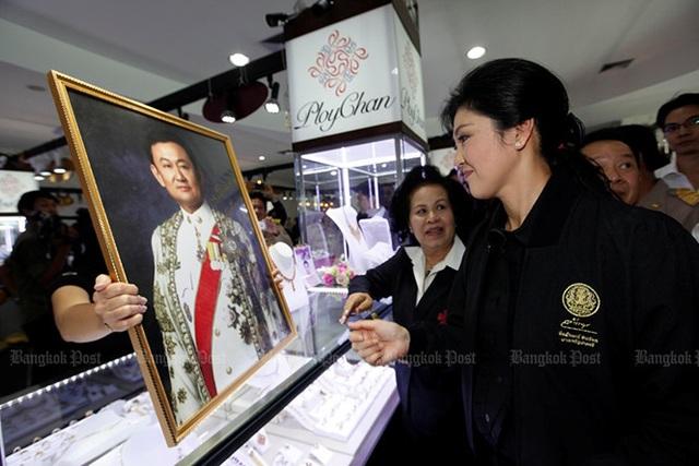 Bà Yingluck kí tên vào bức ảnh của anh trai mình, cựu Thủ tướng Thái Lan đang lưu vong Thaksin Shinawatra tại một cửa hàng trang sức vào ngày 6/11/2013. Ảnh: Bangkok Post