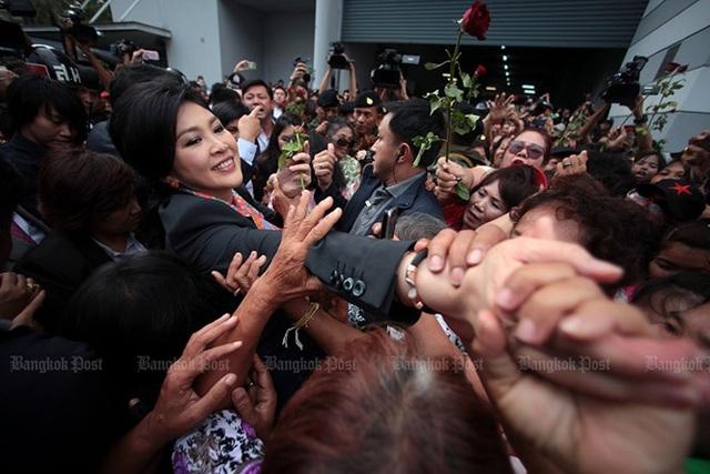 Bà Yingluck được bao vây bởi những người ủng hộ sau khi Tòa án Hiến pháp ra phán quyết bãi chức thủ tướng của Yingluck do thuyên chuyển vi hiến sĩ quan an ninh hàng đầu Thawil Pliensri khỏi chức vụ Tổng thư ký Hội đồng An ninh Quốc gia vào năm 2011. Ảnh: Bangkok Post