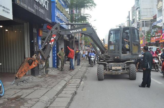Tại tuyến phố Nguyễn Lương Bằng, lực lượng chức năng huy động máy phá bê tông cỡ lớn để xử lý các trường hợp lấn chiếm vỉa hè, lòng đường.