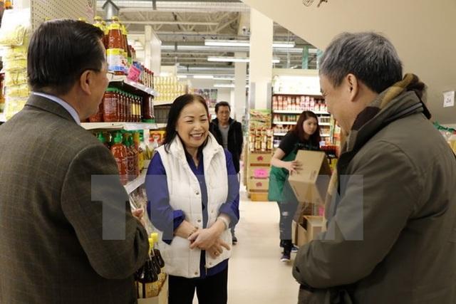 Đại sứ Nguyễn Đức Hòa (phải) và Tổng lãnh sự Phạm Mạnh Hải trao đổi với chủ siêu thị HenLong. (Ảnh: Thúy Hà/TTXVN)