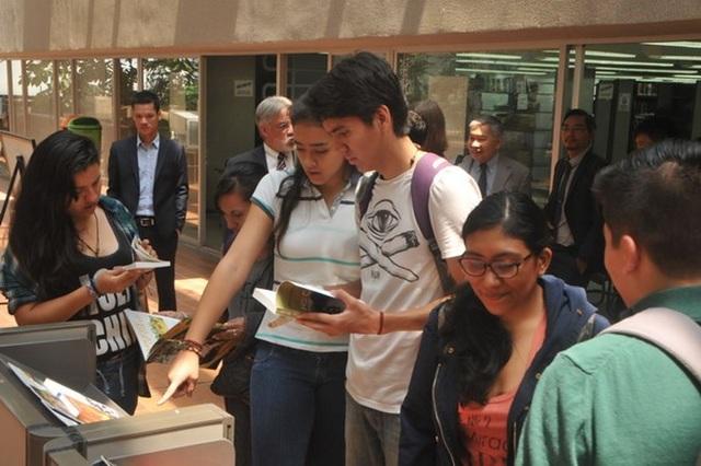Các sinh viên tìm hiểu cuộc đời và sự nghiệp của Bác Hồ qua sách báo triển lãm. (Ảnh: Việt Hùng/Vietnam+)