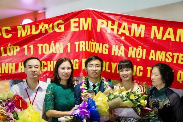 Phạm Nam Khánh (ở giữa, tay cầm huy chương) vui vẻ khoe thành tích bên bà ngoại, bố mẹ và cô giáo.