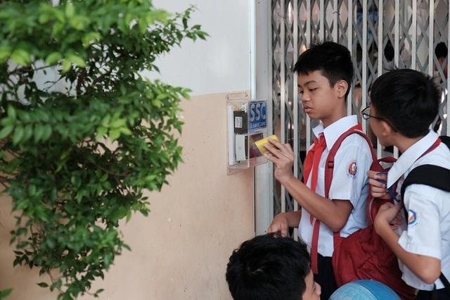 Học sinh quẹt thẻ để điểm danh. (Ảnh: Thanh Tuyền)