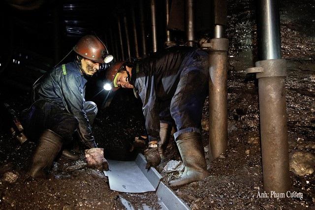 Công nhân lắp đặt máng trượt để tải than