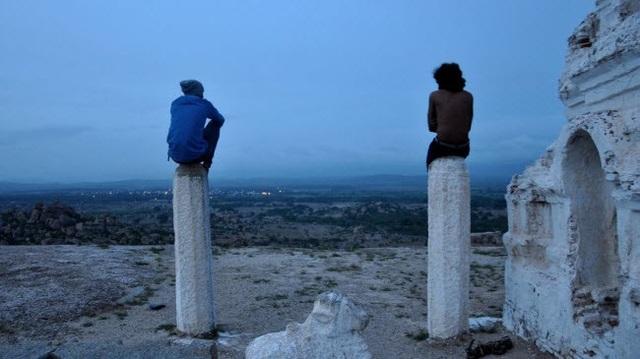 Hai du khách ngồi trên đỉnh trụ đá trong ngôi đền Veerabhadra để chờ ngắm bình minh.