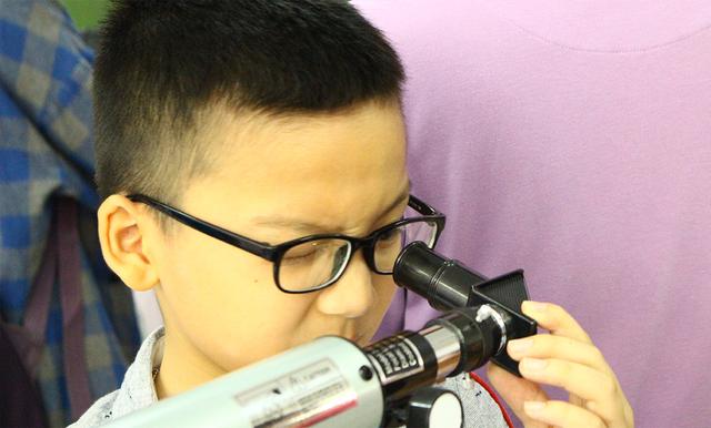 Một bạn nhỏ chăm chú quan sát kính thiên văn.