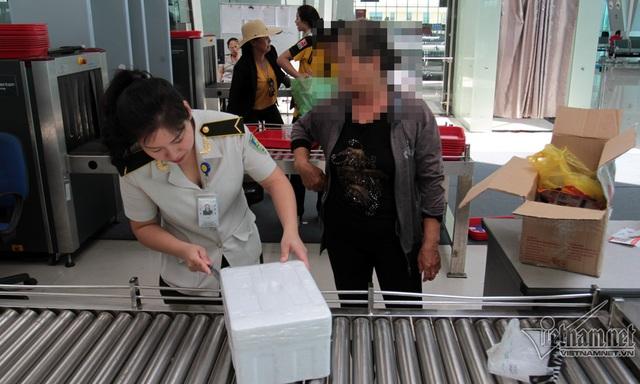 Nhân viên an ninh Phan Thị Yến mở thùng xốp nghi ngờ có nhiều đồ dùng không an toàn. Sau khi mở ra, trong đó là bánh mướt tráng và mấy hũ cà hành khách mang vào TP.HCM làm quà