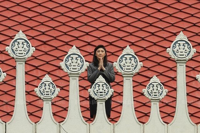 Bà Yingluck (lúc này đã nhậm chức Thủ tướng) đứng trên mái của tòa nhà Chính phủ để cầu xin phước lành từ một ngôi đền thiêng trong ngày đầu làm việc – 16/8/2011. Ảnh: Bangkok Post