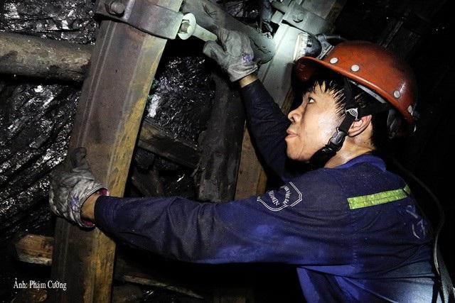 Một người thợ mỏ củng cố vì chống trong hầm lò
