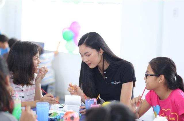 Helly Tống hướng dẫn một em bé tô tượng và lắng nghe em kể về ước mơ của mình.