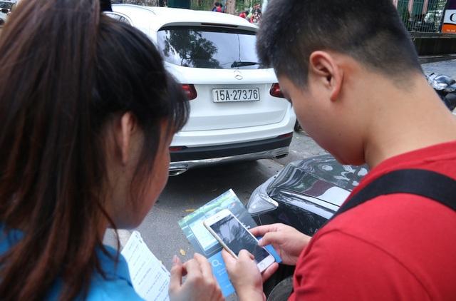 Một nhân viên đang hướng dẫn lái xe thanh toán tiền đỗ xe bằng cách gửi tin nhắn qua điện thoại.
