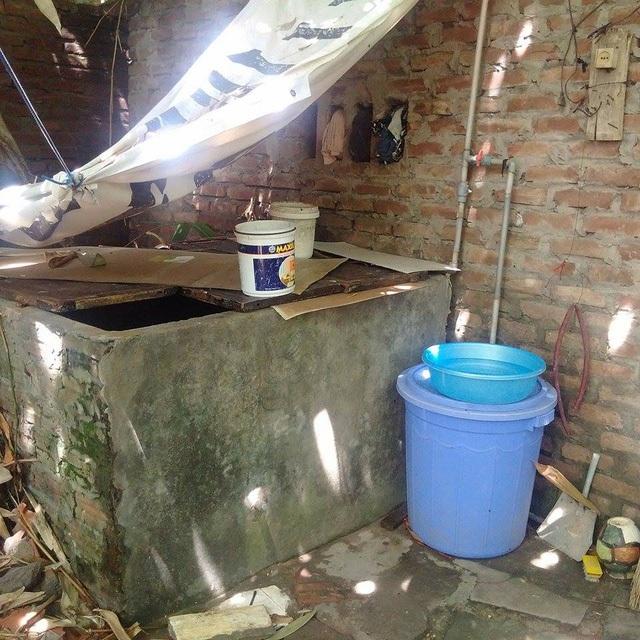 Thùng chứa nước sinh hoạt đặt cạnh nhà vệ sinh, lá tre rụng xuống phủ đầy mặt nước.