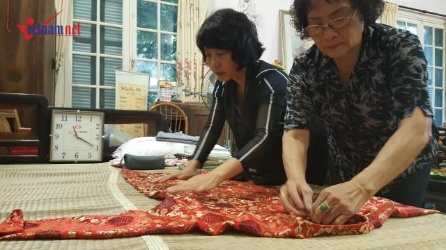 Bà Hà và bà Yến, hai người con dâu của cụ Hoàng Thị Minh Hồ đang xếp lại chiếc áo dài của mẹ. Ảnh: Diệu Bình