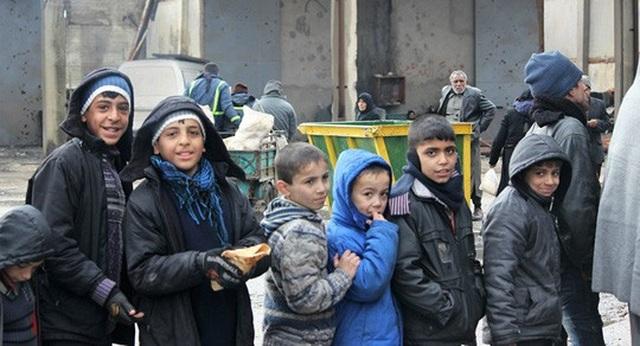 Trẻ em xếp hàng chờ được phát lương thực. Ảnh: Sputnik