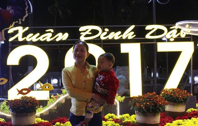 Người phụ nữ bế con lưu lại kỷ niệm ở một điểm trang trí Tết trên đường Trần Phú trước thời khắc đón năm mới Đinh Dậu - Ảnh: Viết Hảo