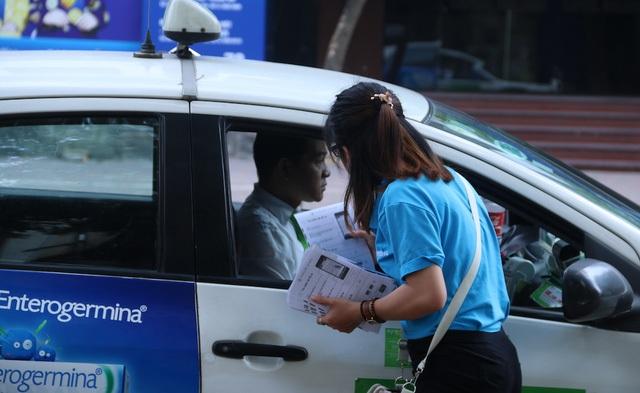 Ngoài việc tư vấn hay trực tiếp hướng dẫn lái xe thanh toán tiền đỗ xe, nhân viên này còn phát tờ rơi để lái xe biết đến dịch vụ đỗ xe thông minh.