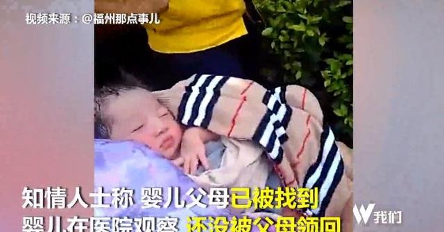 Đứa bé được người qua đường bế trong khi chờ đội ngũ y tế