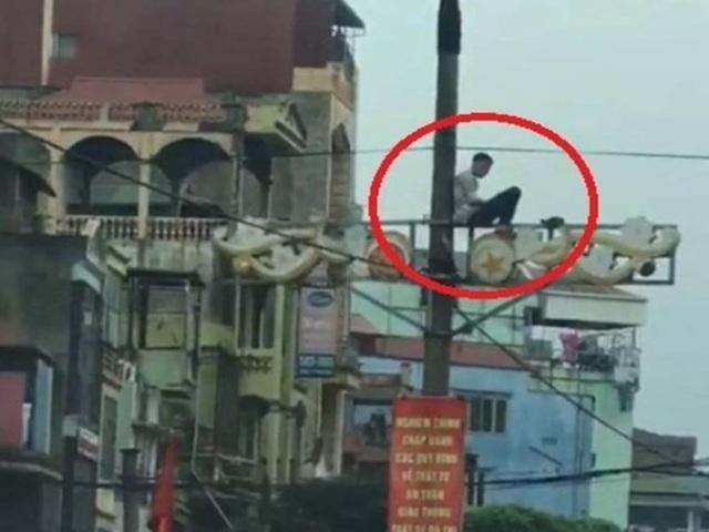 Tại Hà Nội, một thanh niên ngáo đá khác leo lên cột điện ngồi (Ảnh IT)