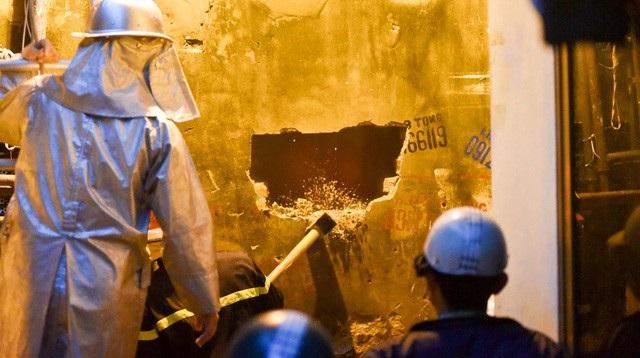 Phía sau của tòa nhà, lực lượng chữa cháy dùng búa tạ phá tường để bơm nước chữa cháy.