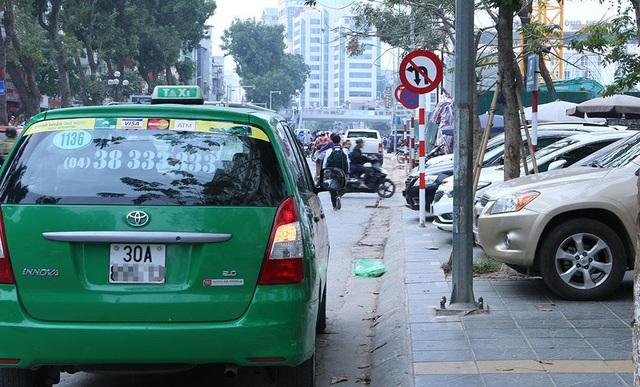 Cảnh xe ô tô, taxi dừng đỗ trái phép trên phố Giảng Võ hướng đi phố Láng Hạ trong giờ nghỉ trưa. Dọc tuyến phố Giảng Võ có nhiều quán ăn, cà phê, toà nhà công sở nên tình trạng các phương tiện dừng đỗ trái phép thường xuyên diễn ra.