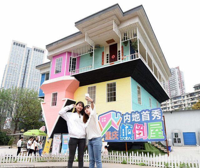 Du khách chụp ảnh trước một ngôi nhà lộn ngược nhiều màu sắc ở thành phố Trùng Khánh, Trung Quốc.
